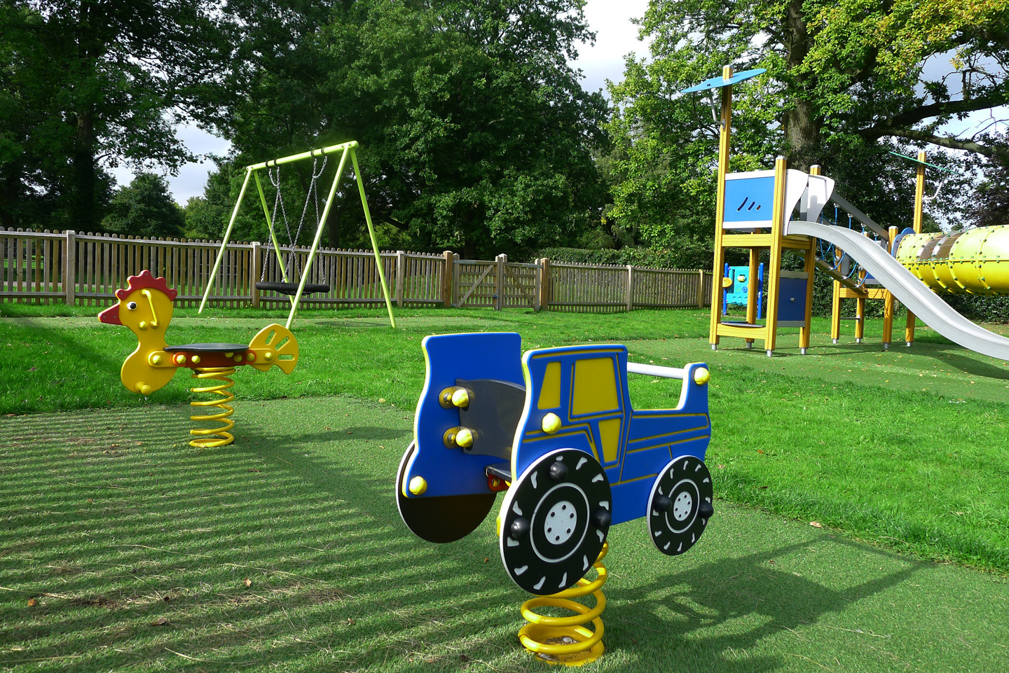 childrens play area featuring swings and slide