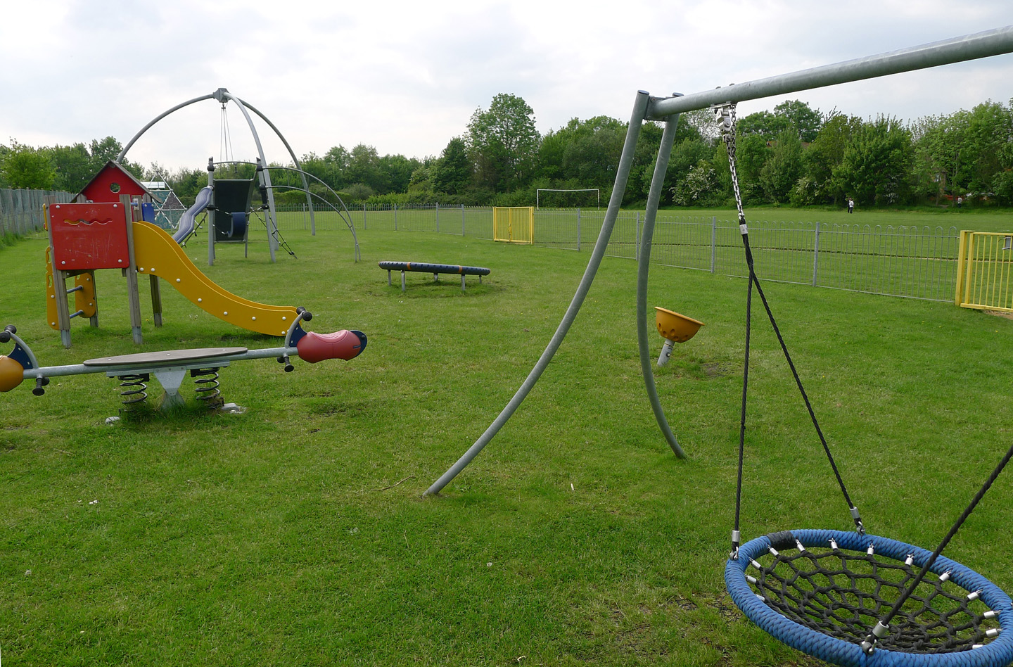 play area at paddock way featuring a seesaw swing and slide