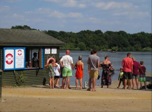 People stood beside boat shed at Petersfield Heath