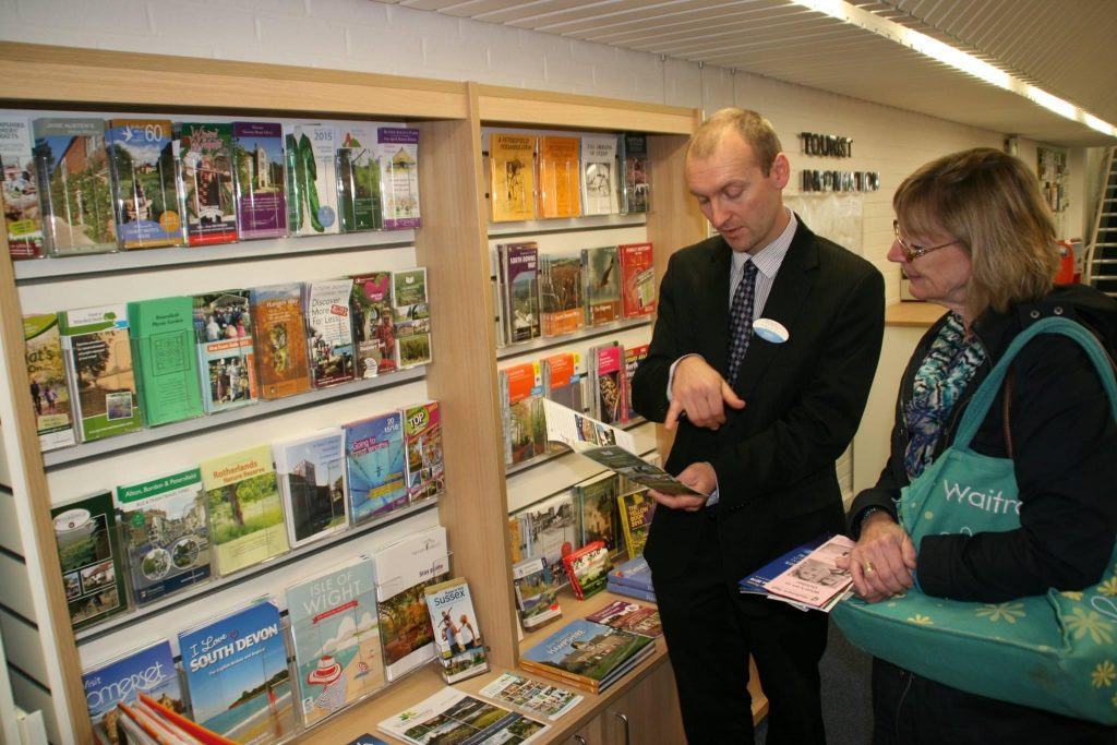 tourist centre manager assisting a member of the public